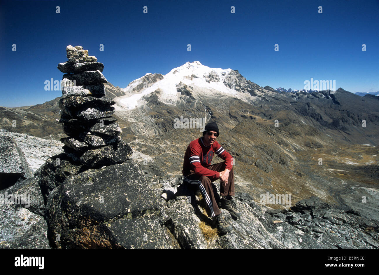 Trekker and cairn, Mount Huayna Potosi in background, Cordillera Real, Bolivia Stock Photo