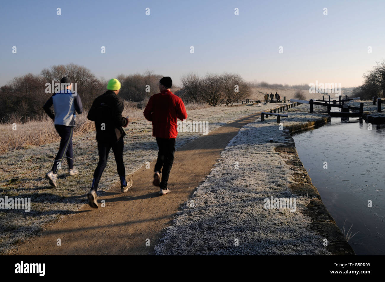 Three Joggers running along the towpath Chesterfield Canal Derbyshire England UK - Stock Image