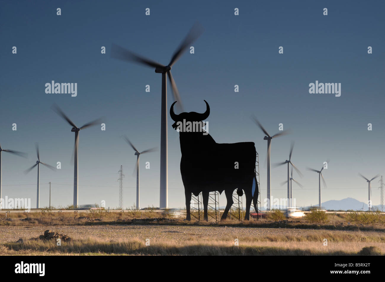Two cars are a blurr beneath Wind turbines and the Spanish roadside bull or Toro de Osborne in Spain - Stock Image