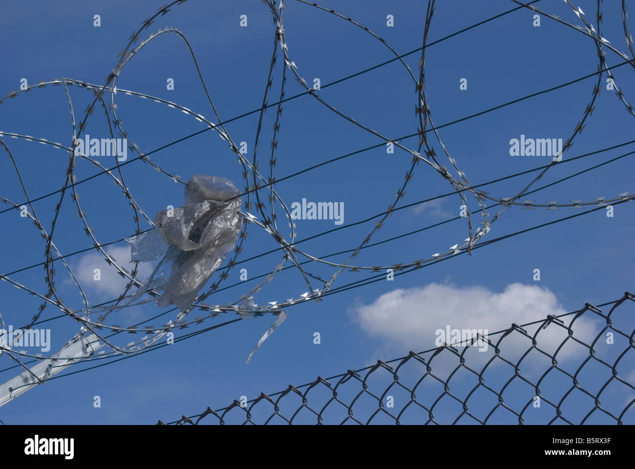 Barbed Wire Fence With Rubbish Stock Photos & Barbed Wire Fence With ...