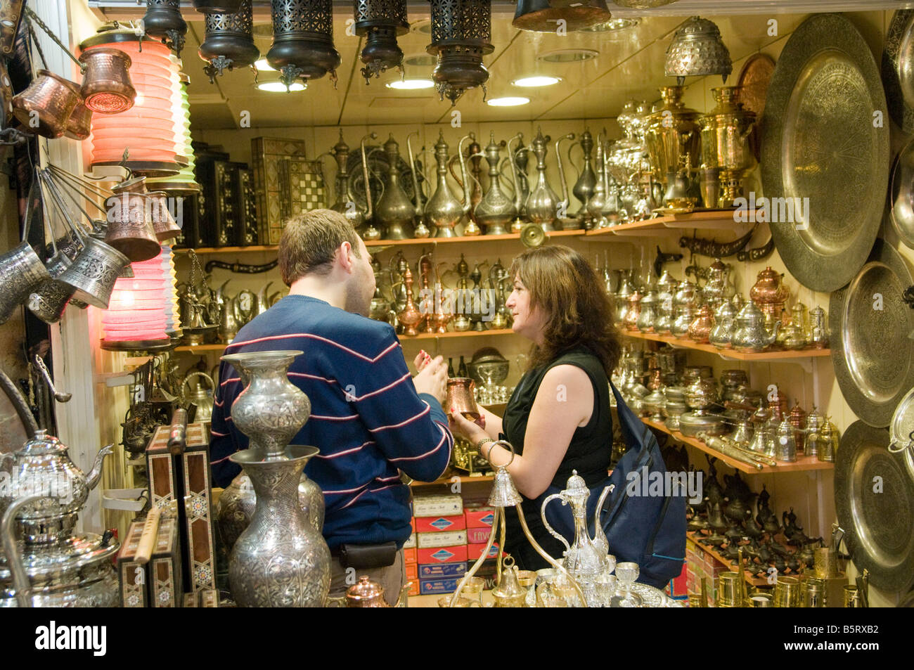 Turkey Istanbul The Grand Bazaar Copper handwork stall female tourist haggling with the vendor - Stock Image
