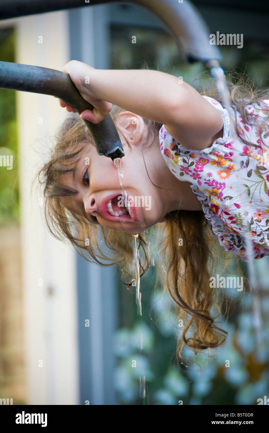 Girl drinking water from a water fountain. - Stock Image