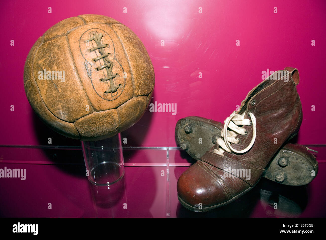 An old pair of football boots antique leather soles and studs with an old leather football at Nou Camp, Barcelona - Stock Image