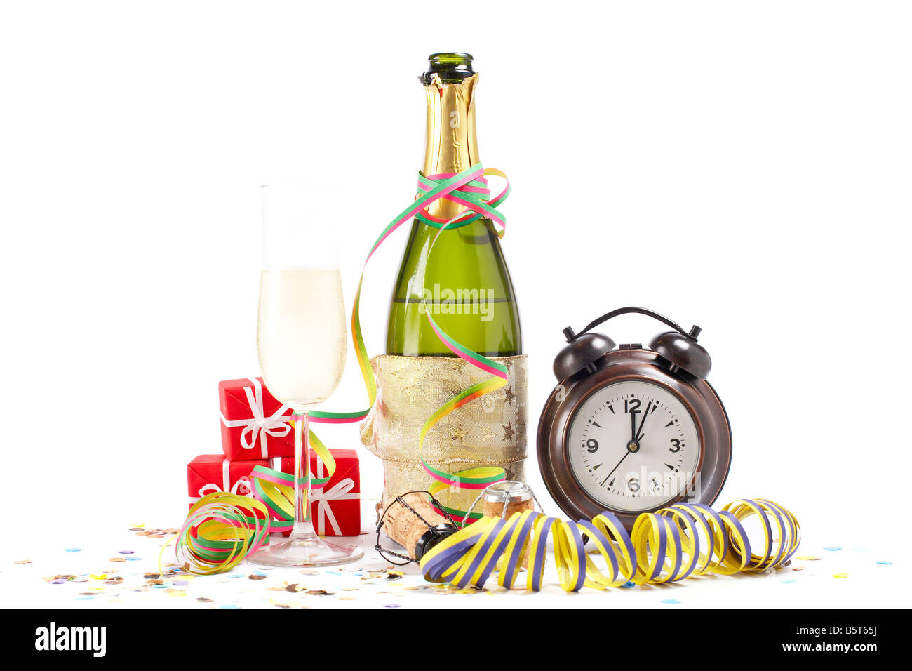 champagne glass ready to bring in the new year with clock ribbons and confetti stock