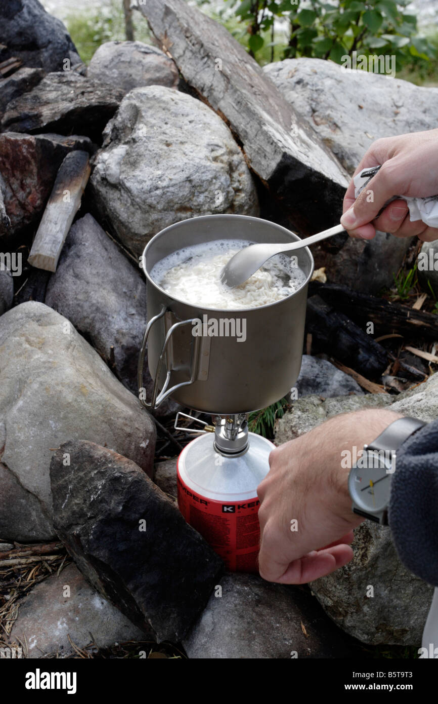 Backpacker cooking lunch on a camping stove in Sweden. This was taken in Töfsingdalen, Dalarna. - Stock Image