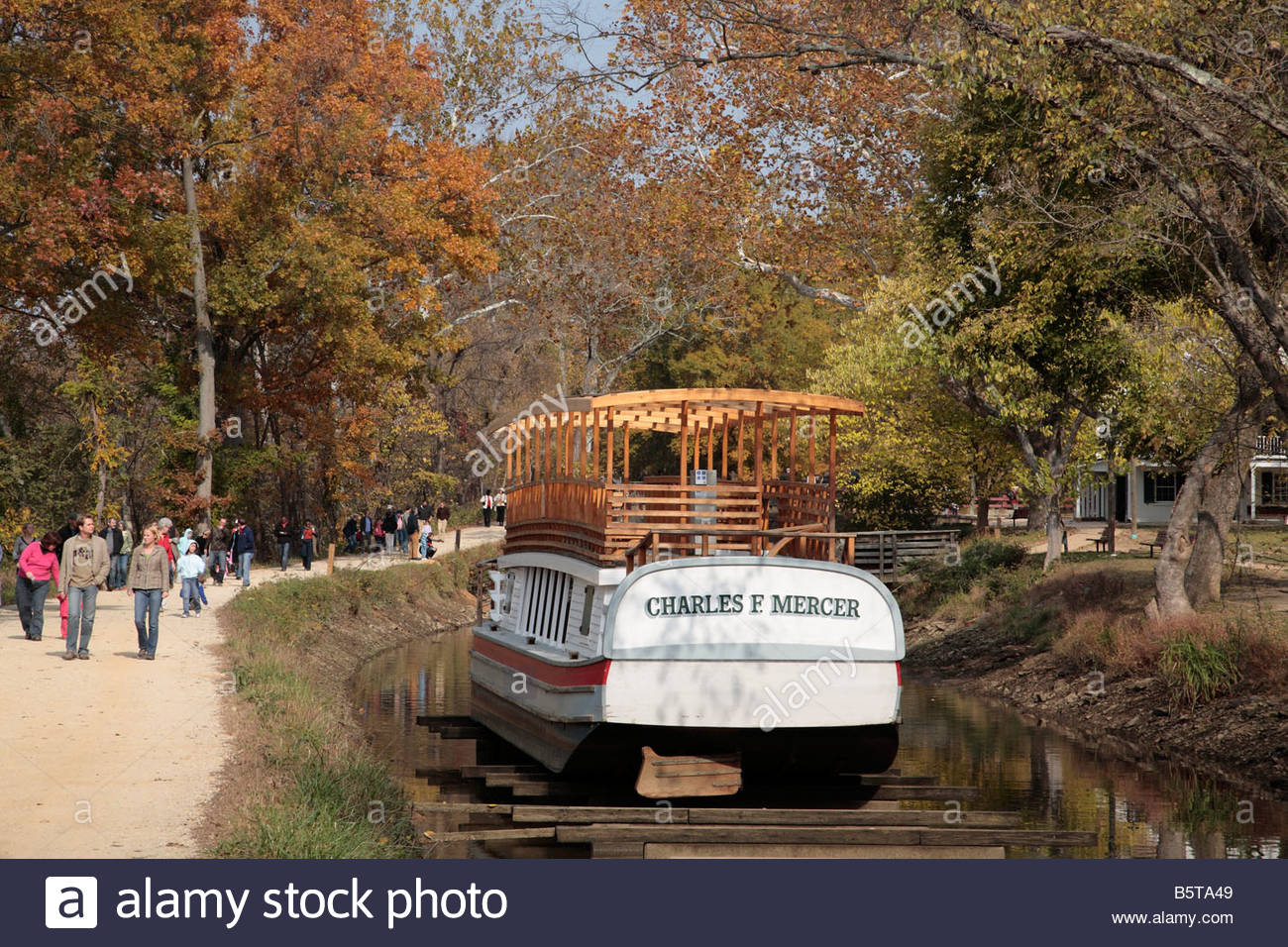 Hikers on the C&O Canal towpath in Maryland pass a drydocked canal boat near Great Falls Tavern. - Stock Image