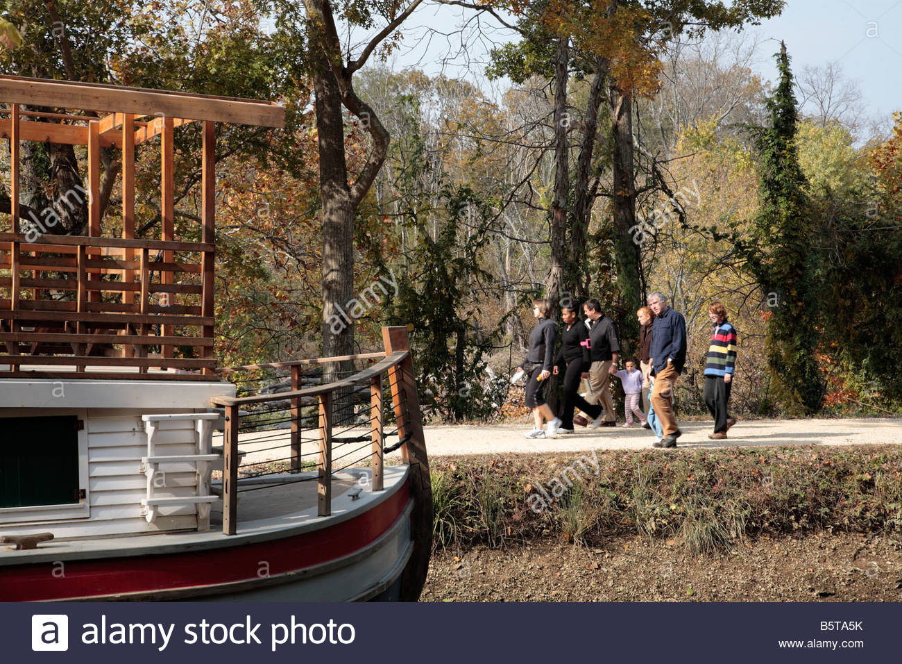 Hikers on the C&O Canal towpath in Maryland pass a drydocked canal boat. - Stock Image