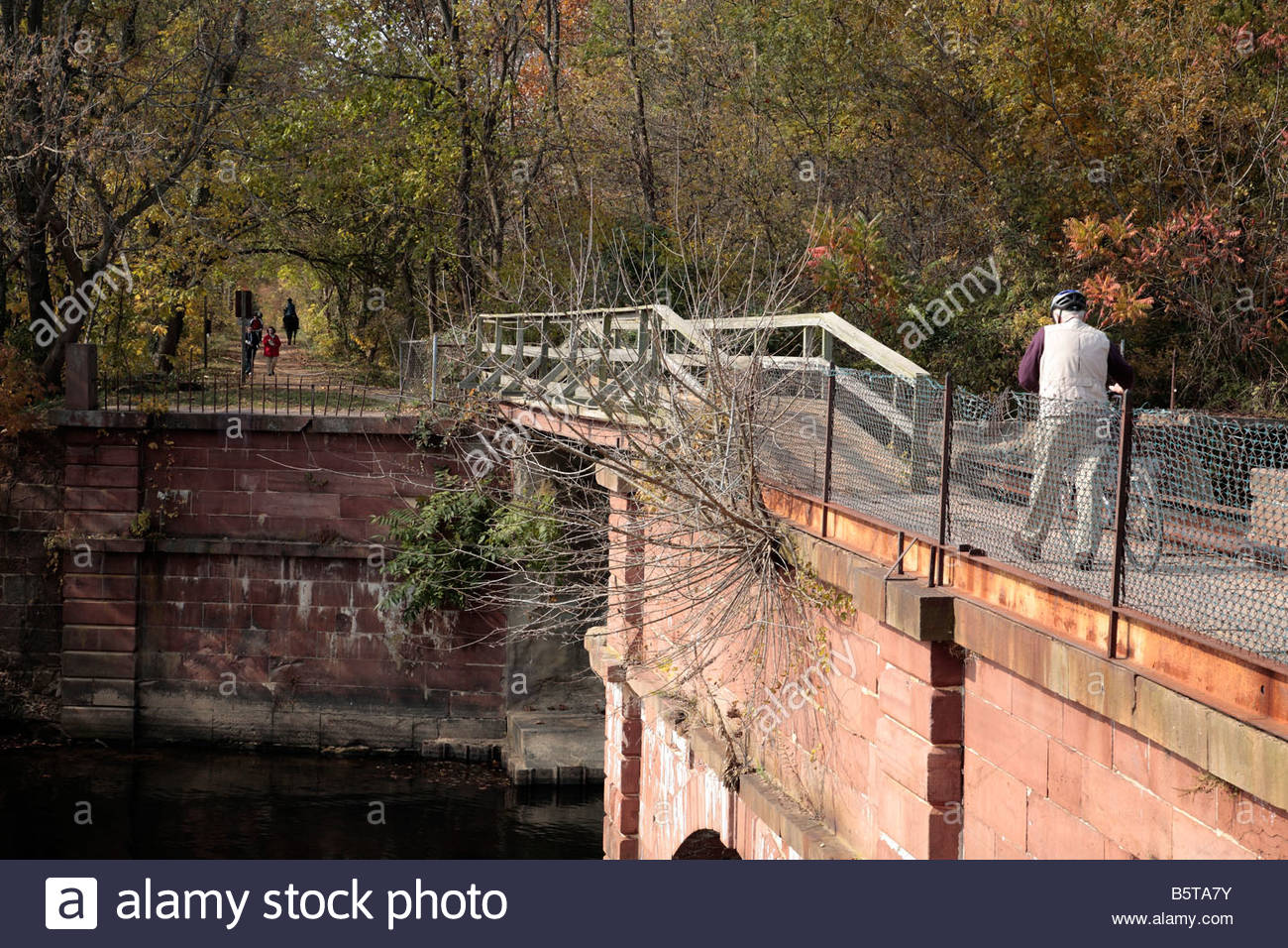 A cyclist, hikers and an equestrian use the C&O Canal towpath at Rileys Lock in Maryland. - Stock Image