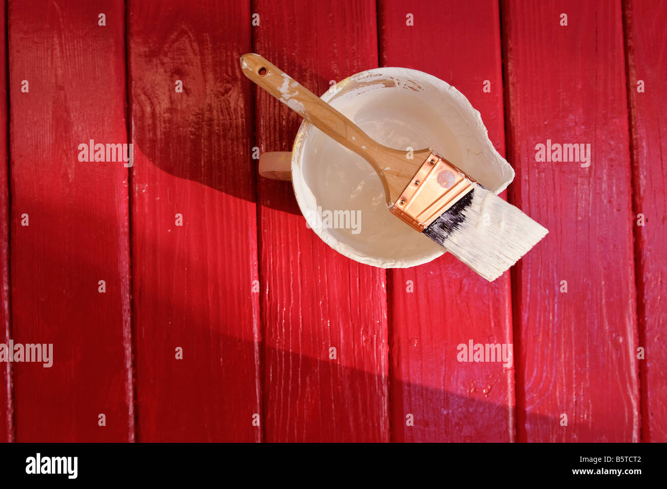 Paint brush, pail and white paint on freshly painted red floor - Stock Image
