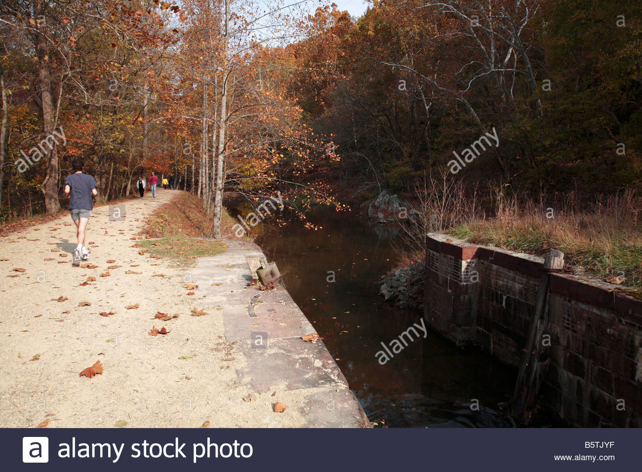 Hikers and a runner on the C&O Canal towpath near Lock 16 in Maryland. - Stock Image