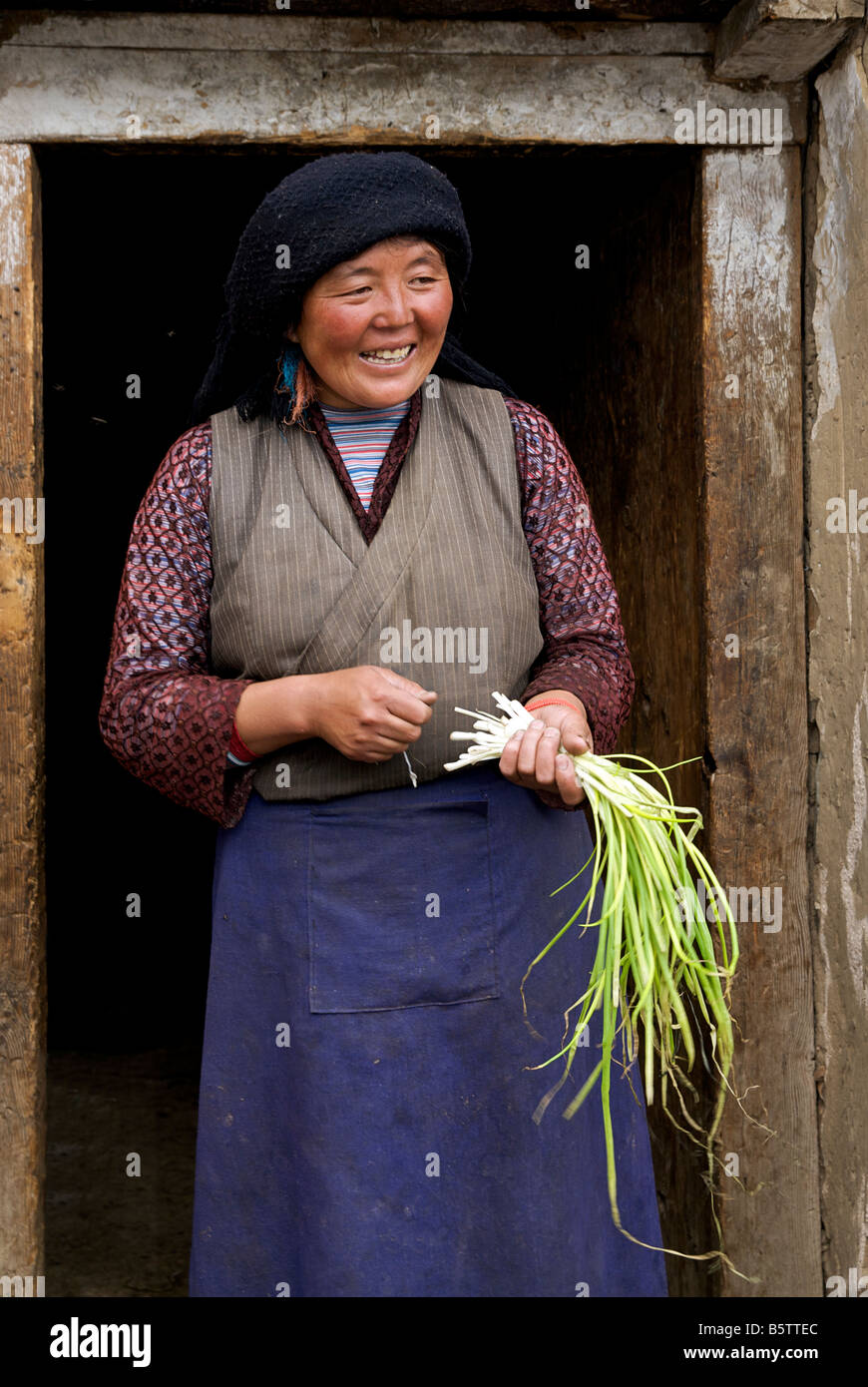 Tibetan woman from rural hamlet at door to home holding handful of spring onions. Tibet - Stock Image