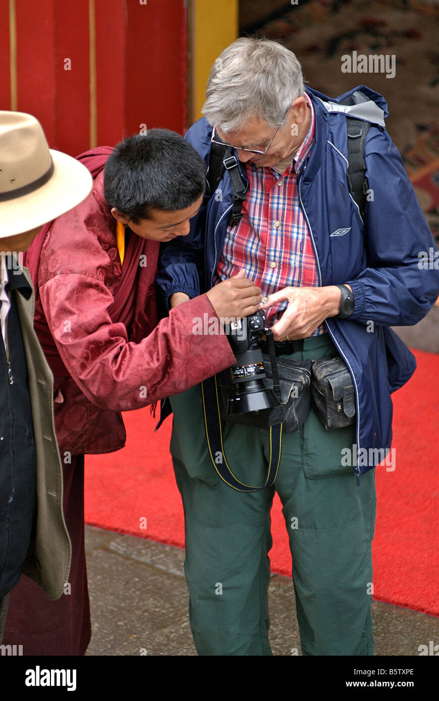 Western tourist photographer sharing his photos with Tibetan locals. Lhasa, Tibet. European subject only model released - Stock Image