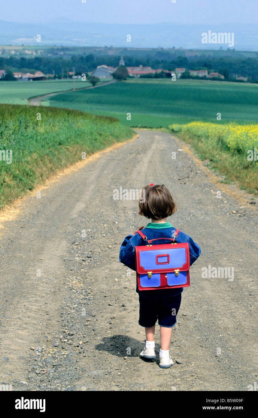 Little girl walking along a country road going to the village school in the countryside Stock Photo