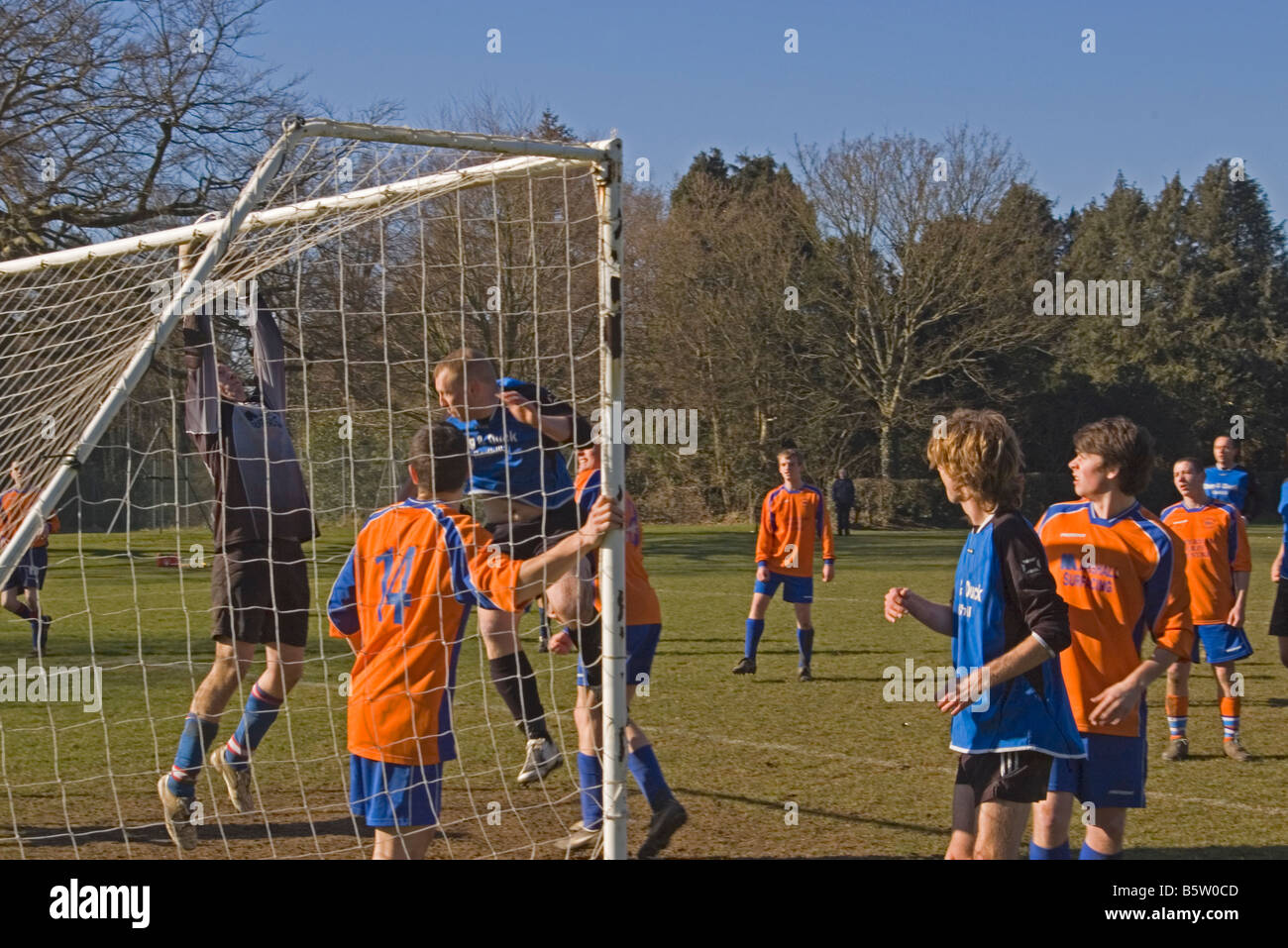 Amateur sunday league Football Match Goalkeeper Catching the Ball Footballers players - Stock Image