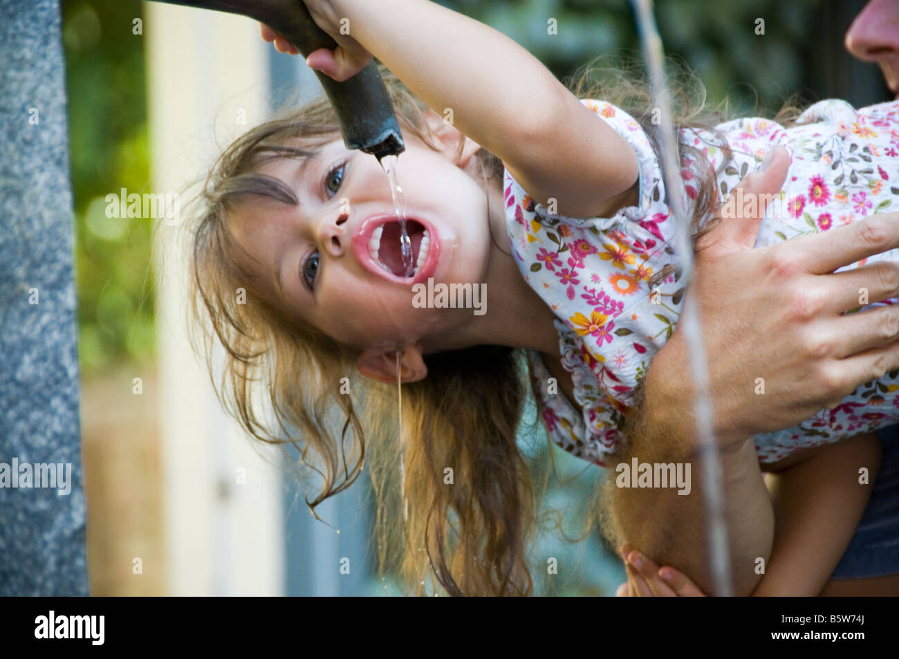 Girl being held while drinking water from a water fountain. Stock Photo