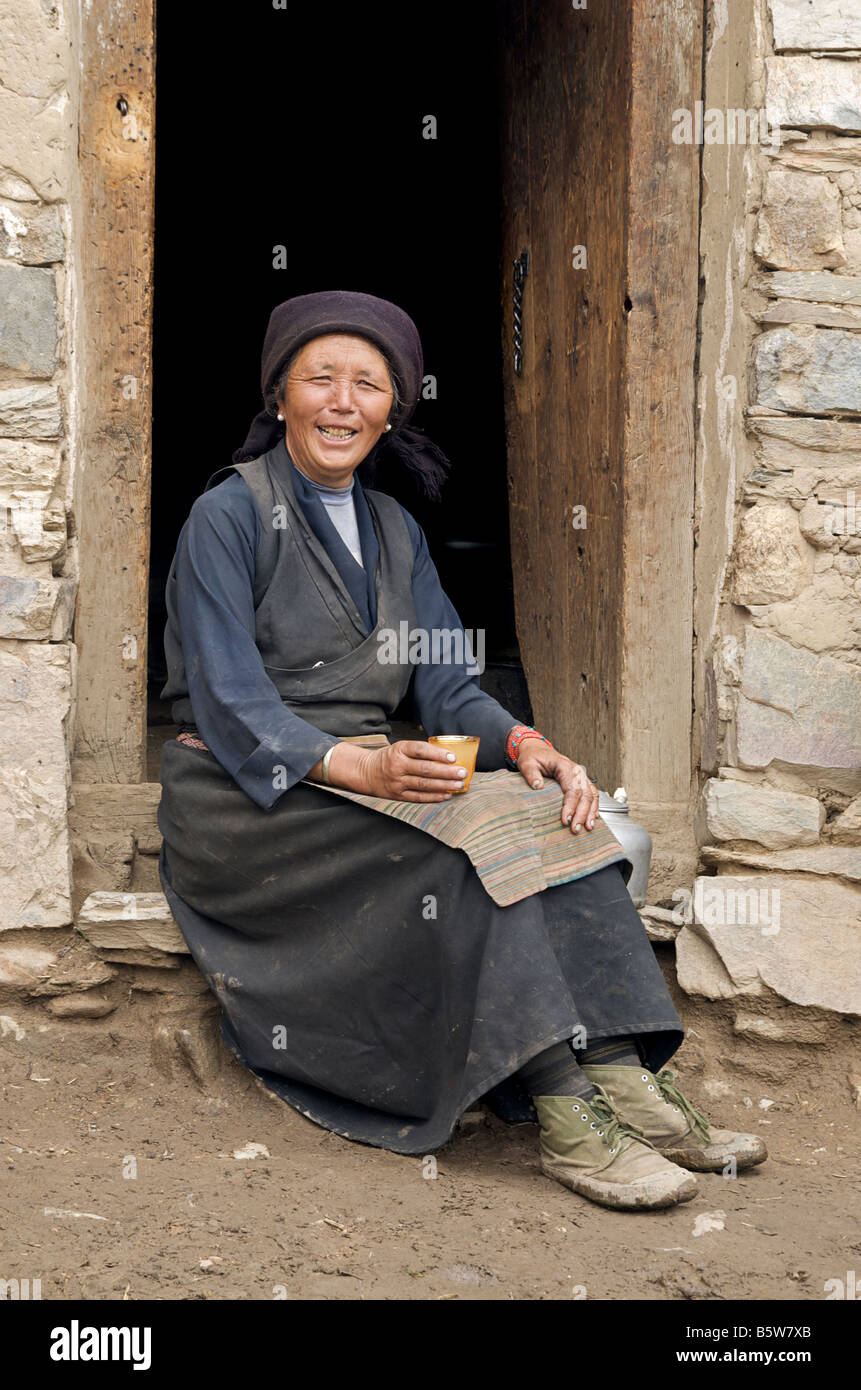 Friendly Tibetan woman sitting at the door to her home and sipping locally brewed beverage. Tibet - Stock Image