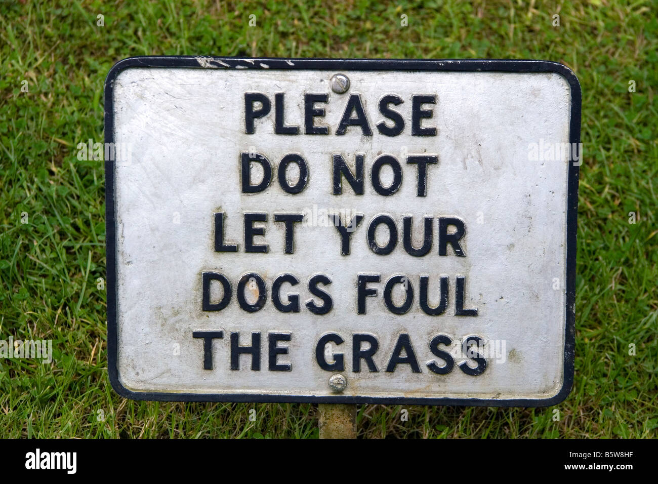 A sign reading please do not let your dogs foul the grass in the village of Bibury Gloucestershire England - Stock Image