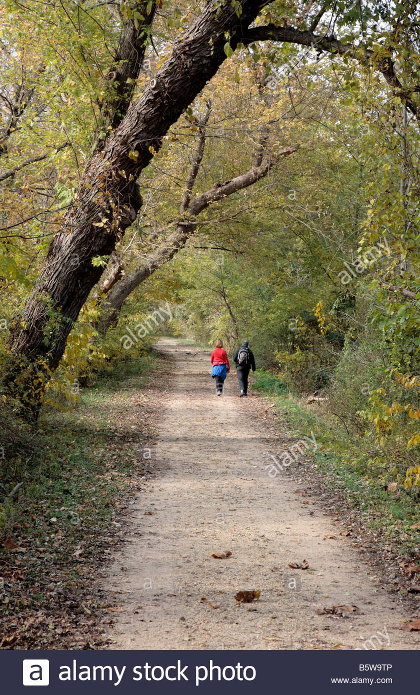 A couple of hikers walk the towpath on the C&O Canal in Maryland. - Stock Image