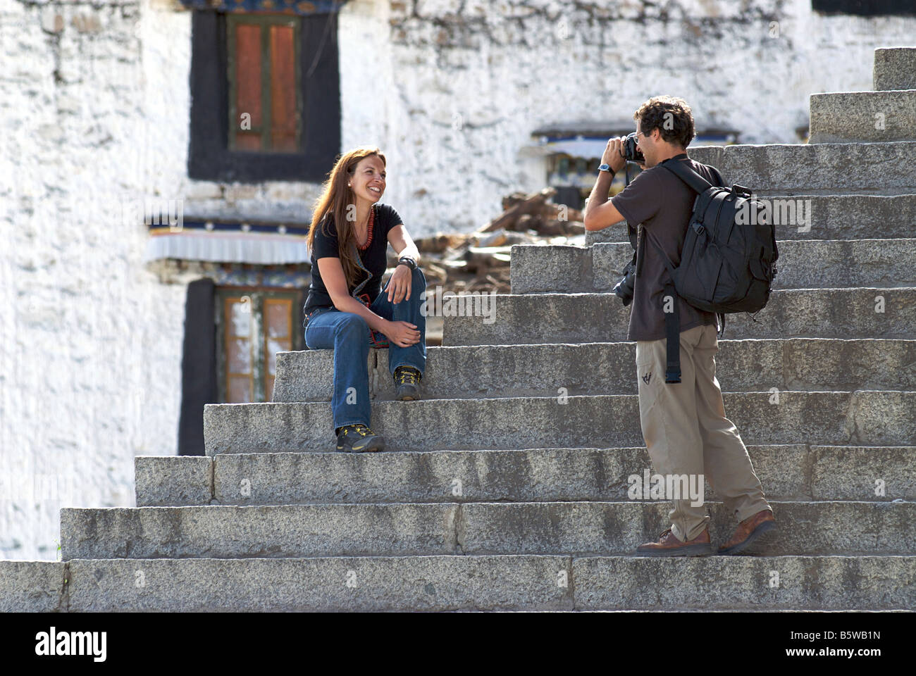 Photographer photographing a friend on the steps of Drepung Monastery, Lhasa, Tibet. Model Released - Stock Image