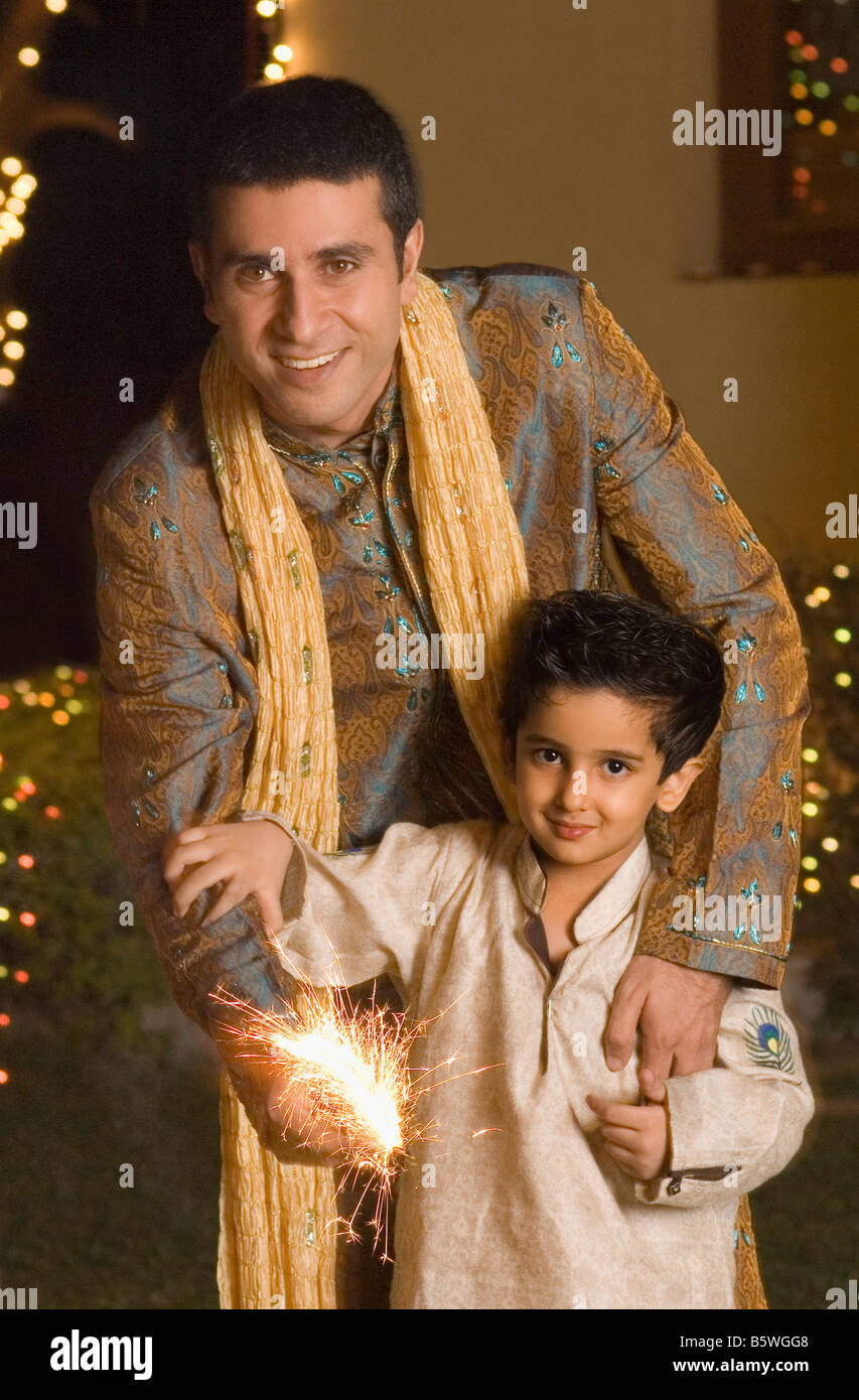 Man celebrating diwali with his son - Stock Image