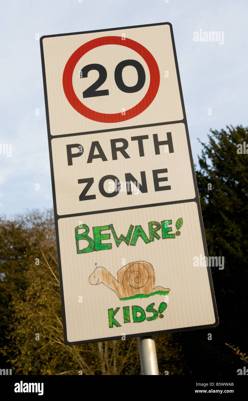 20 mph speed limit zone with hand made Beware Slow Kids snail image added to warn drivers of children in road Brecon - Stock Image