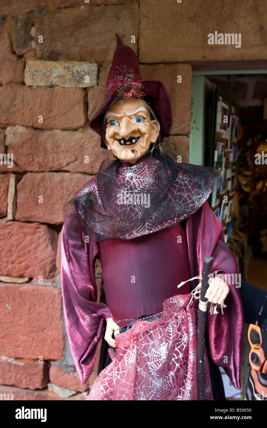 Witch outside shop with pointed hat and snarl + crocked nose, red purple dress  Vertical 87609_Halloween - Stock Image