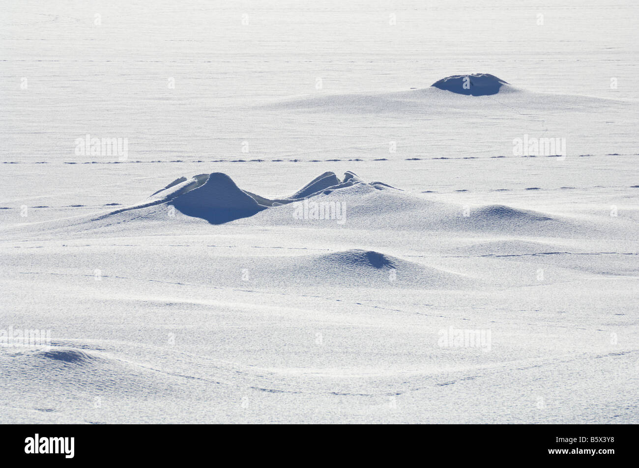 Snow covered lake with distorted ice hummocks and animal tracks Valdres Norway - Stock Image