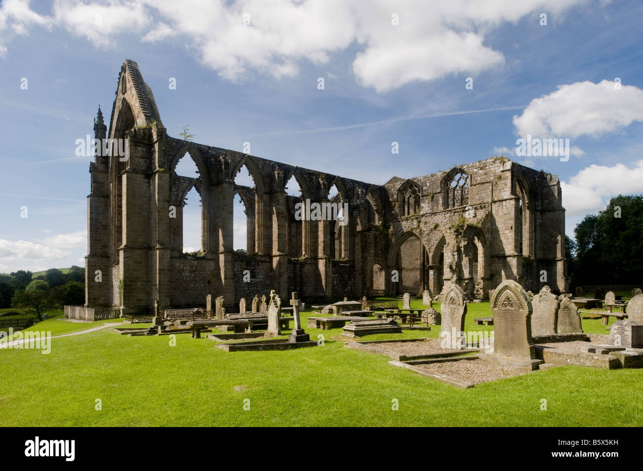 Bolton Priory towers over its graveyard. - Stock Image