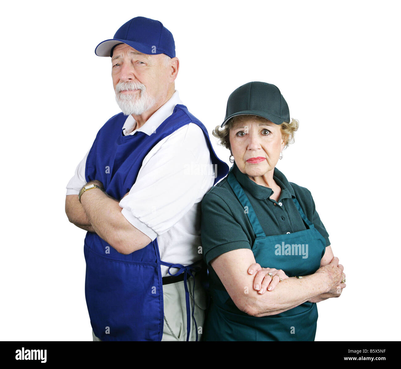 Unhappy senior couple forced to work menial service jobs because of poor retirement planning Isolated on white - Stock Image