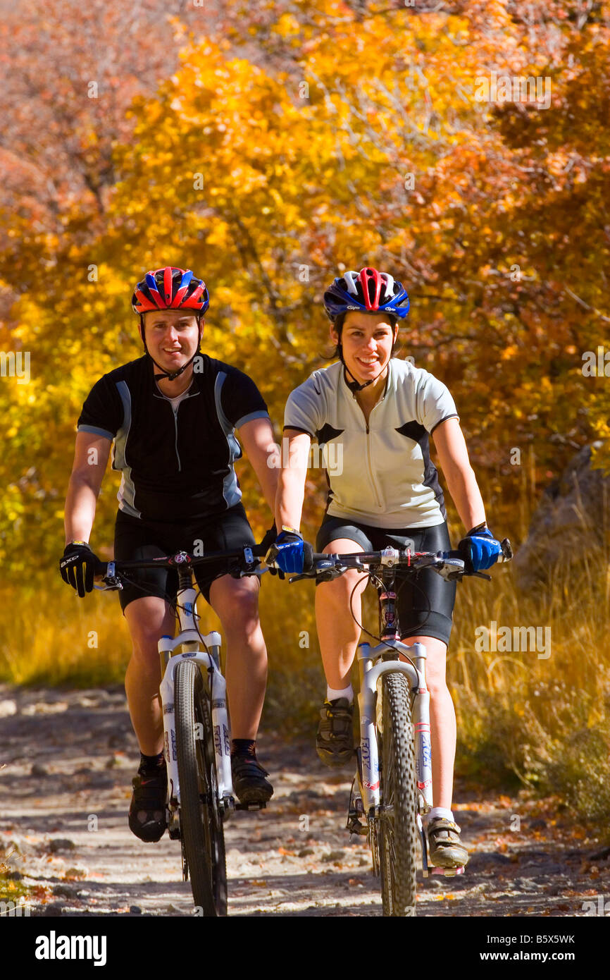 Young couple mountain biking riding amid the autumn colors on the Temple Quarry Trail in Little Cottonwood Canyon - Stock Image