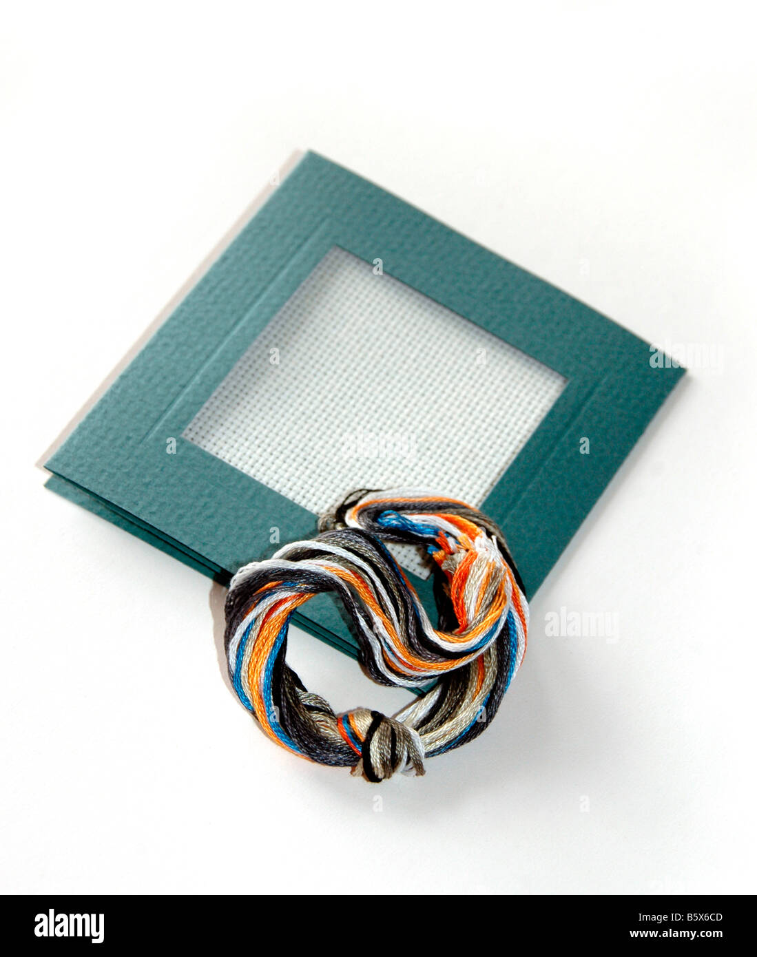 67aae48fff A miniature tapestry frame with a selection of coloured threads. - Stock  Image