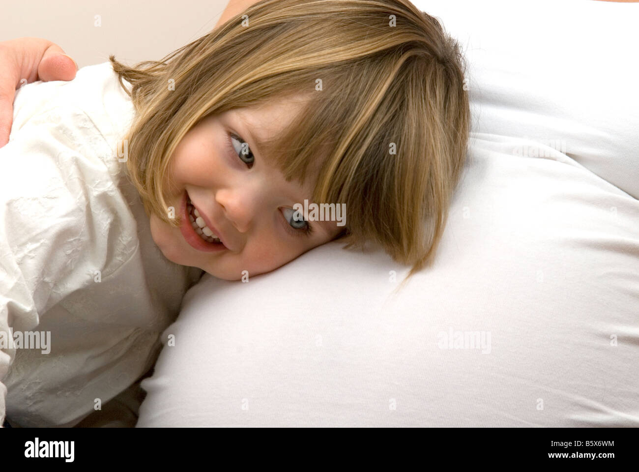 Young girl listens to her mothers pregnant tummy. - Stock Image