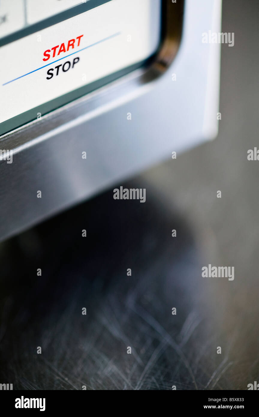 details of a stainless steel microwave oven on a stainless steel counter - Stock Image