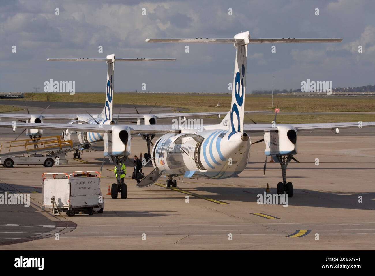 Short-haul air travel. Flybe Bombardier Dash 8-Q400 regional airliners on the ramp at Paris Charles de Gaulle airport. - Stock Image