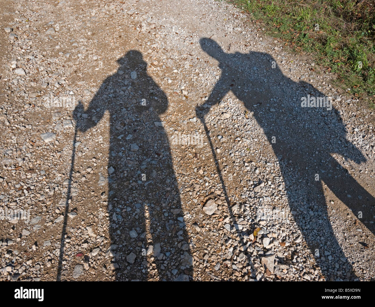shadow of two persons by hiking walking on a treck - Stock Image