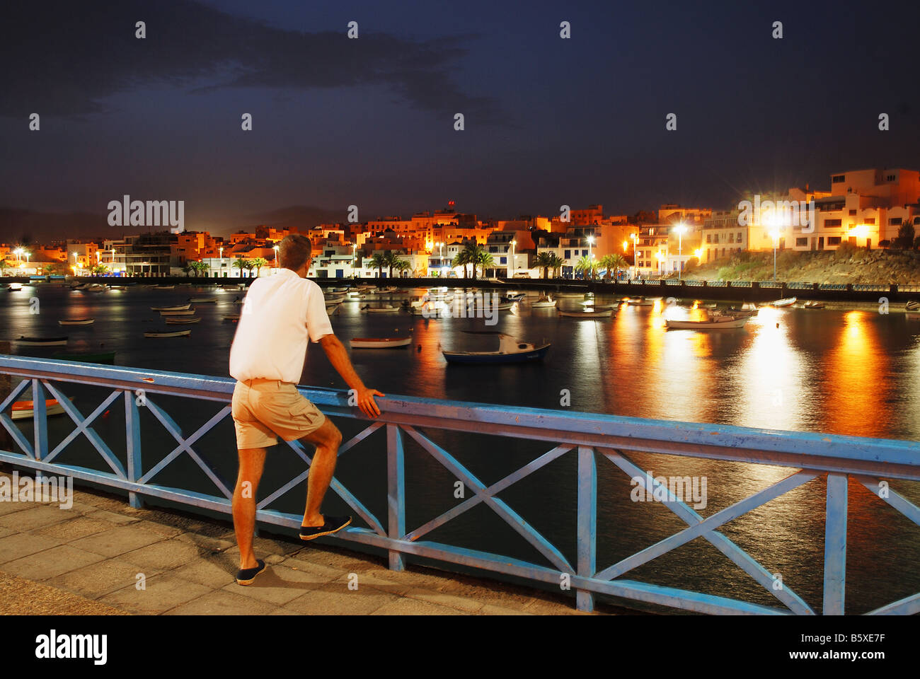 Man leant on banister looking at Charco de San Ginés. Night view. Arrecife. Lanzarote island. Canary Islands. - Stock Image