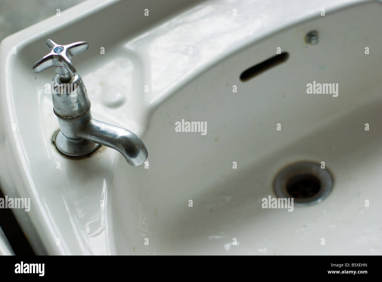 Old Fashioned White Enamel Sink With Chrome Tap Dripping Water