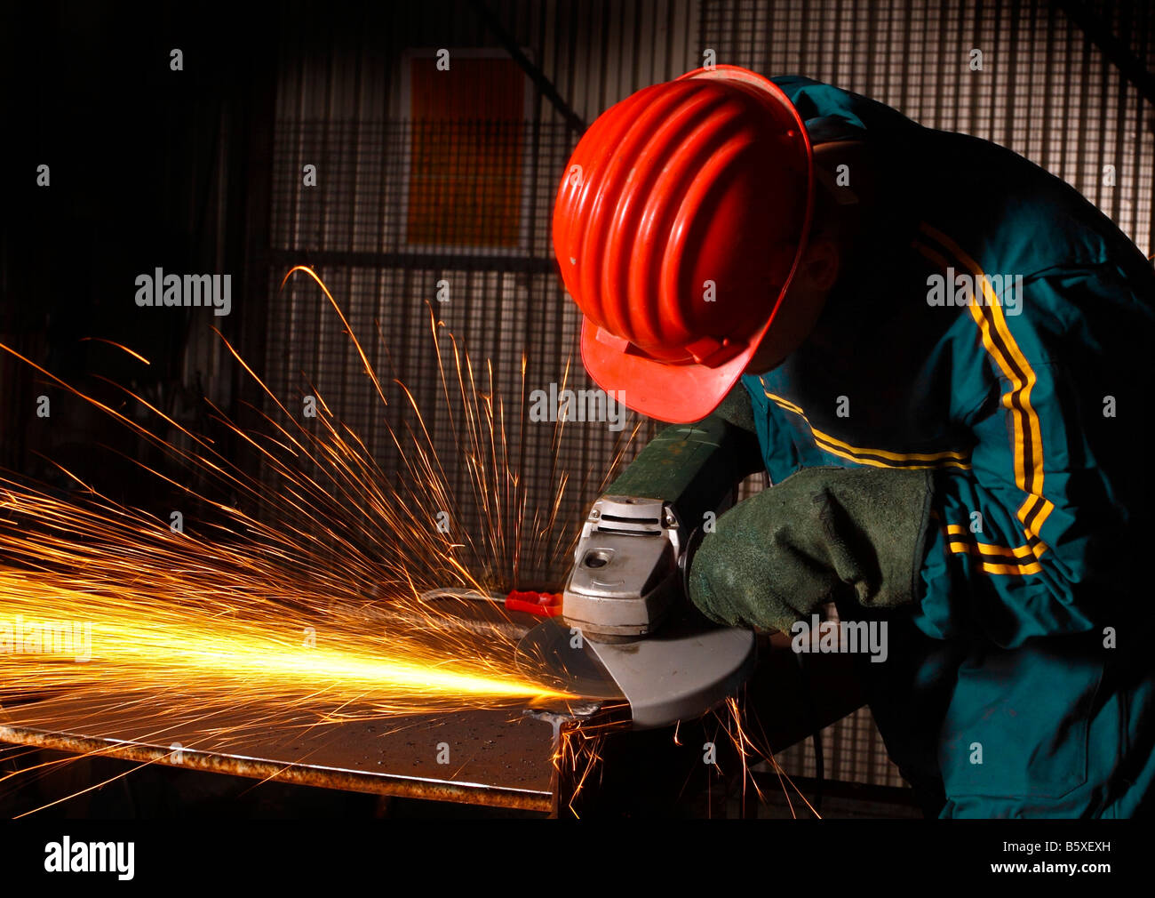 heavy industry manual worker with grinder - Stock Image