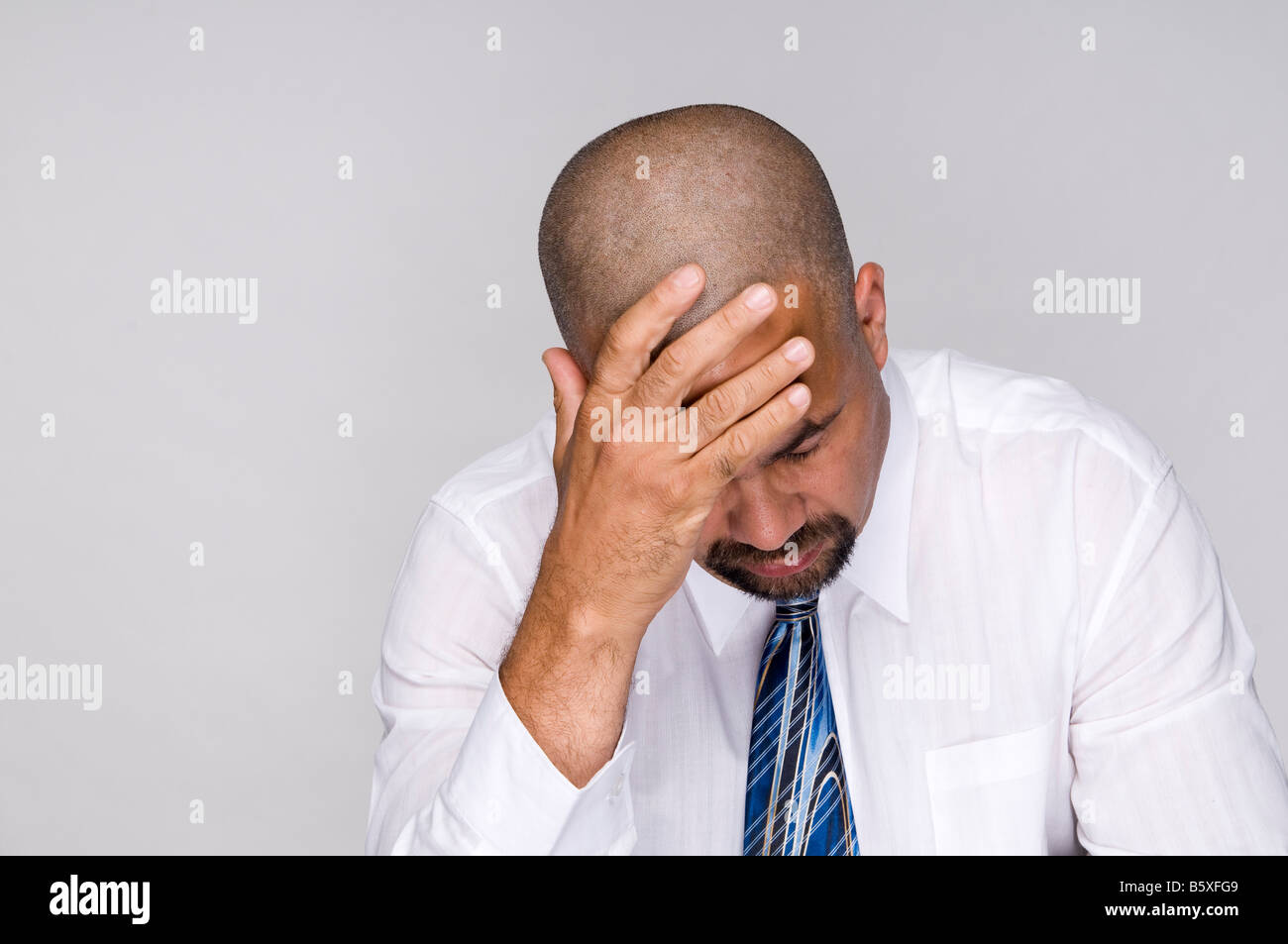 Depressed out of work business man holding head in despair. - Stock Image