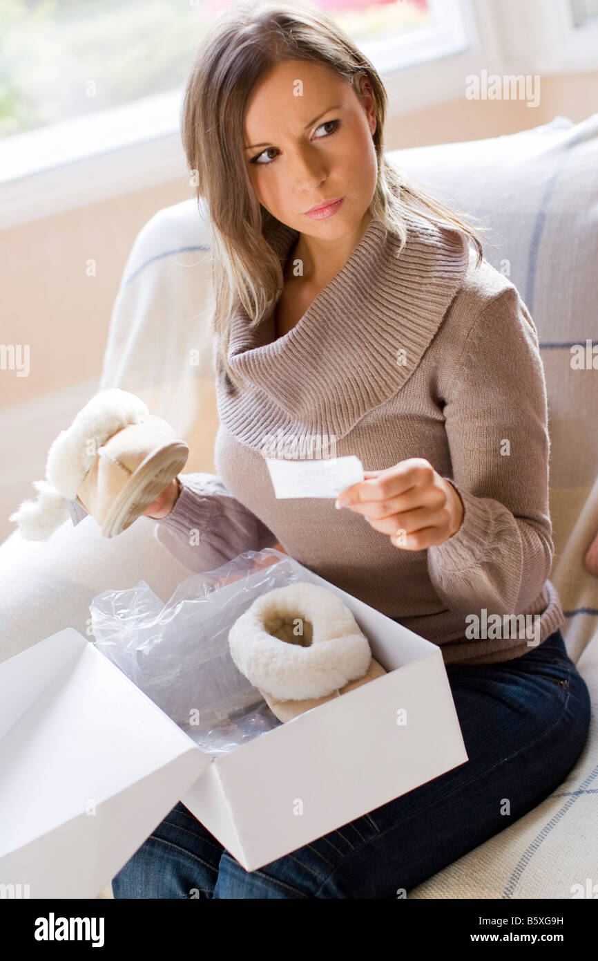 Woman with receipt checking goods - Stock Image