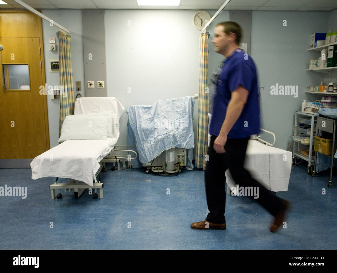 A doctor walks past empty beds at an NHS hospital in UK - Stock Image