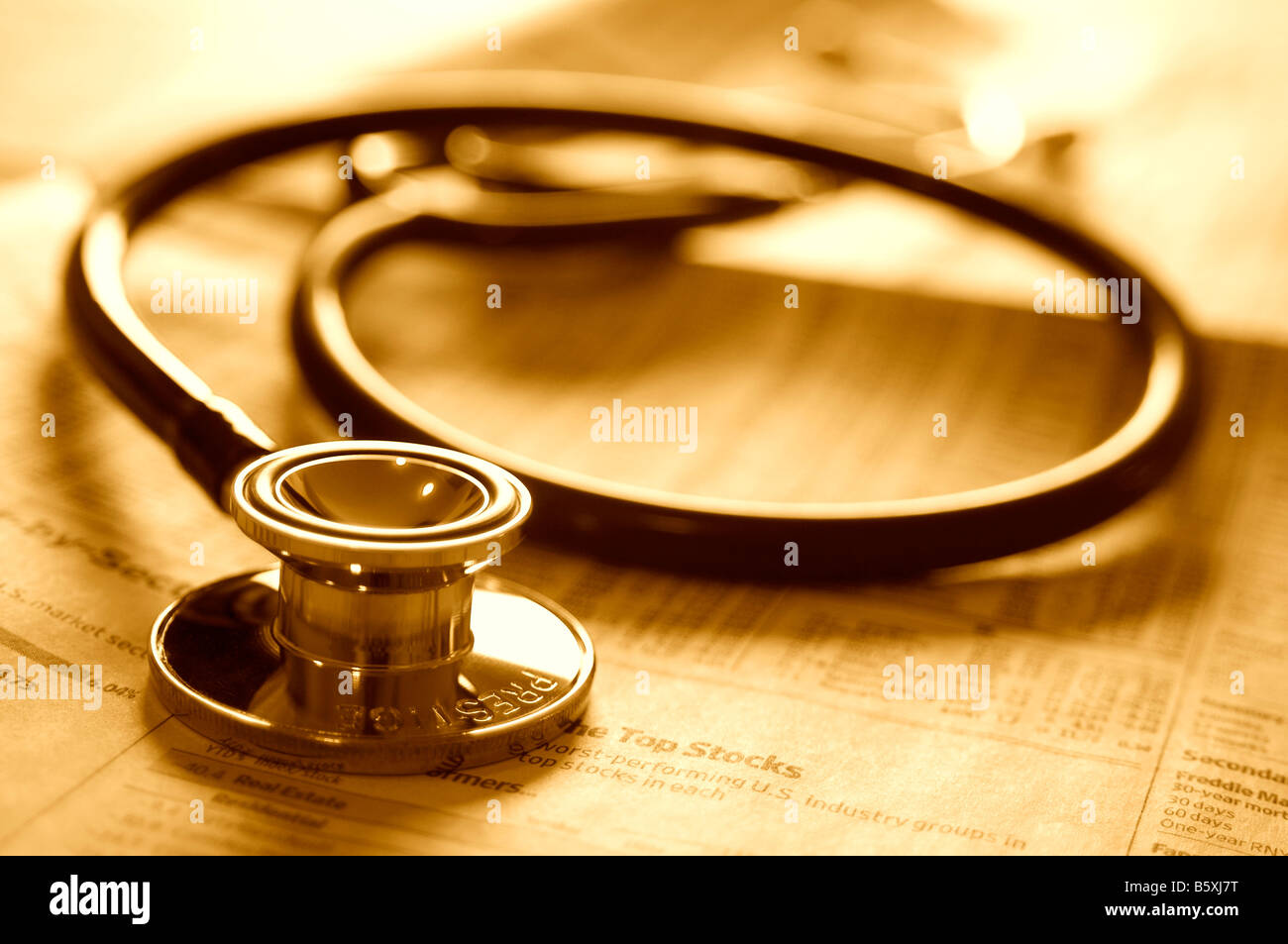 Doctor's stethoscope on investment business newspaper. - Stock Image