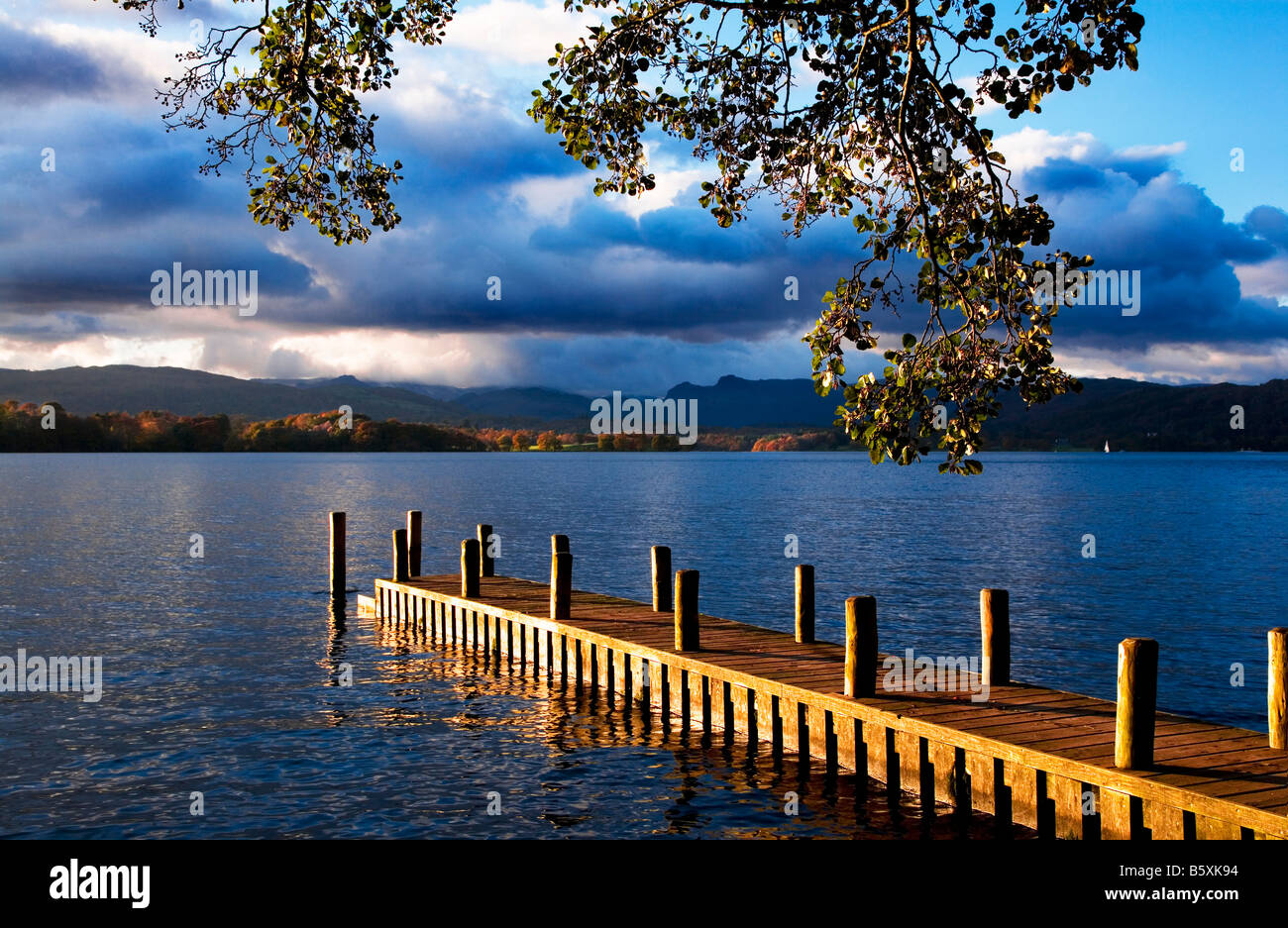 Late afternoon sunshine on jetty, eastern shore Lake Windermere, Langdale Pikes in the distance Lake District Cumbria - Stock Image