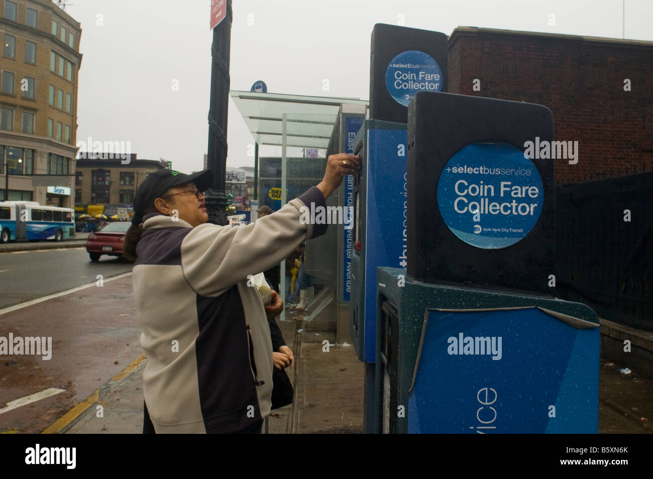 A commuter purchases her fare at a Select Bus Service kiosk in the New York borough of the Bronx - Stock Image