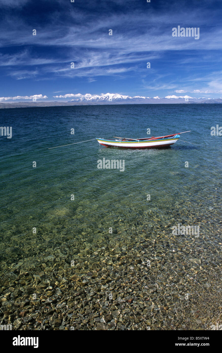 Fishing boat and clear water on pebbles, Cordillera Real in background, Moon Island, Lake Titicaca, Bolivia - Stock Image