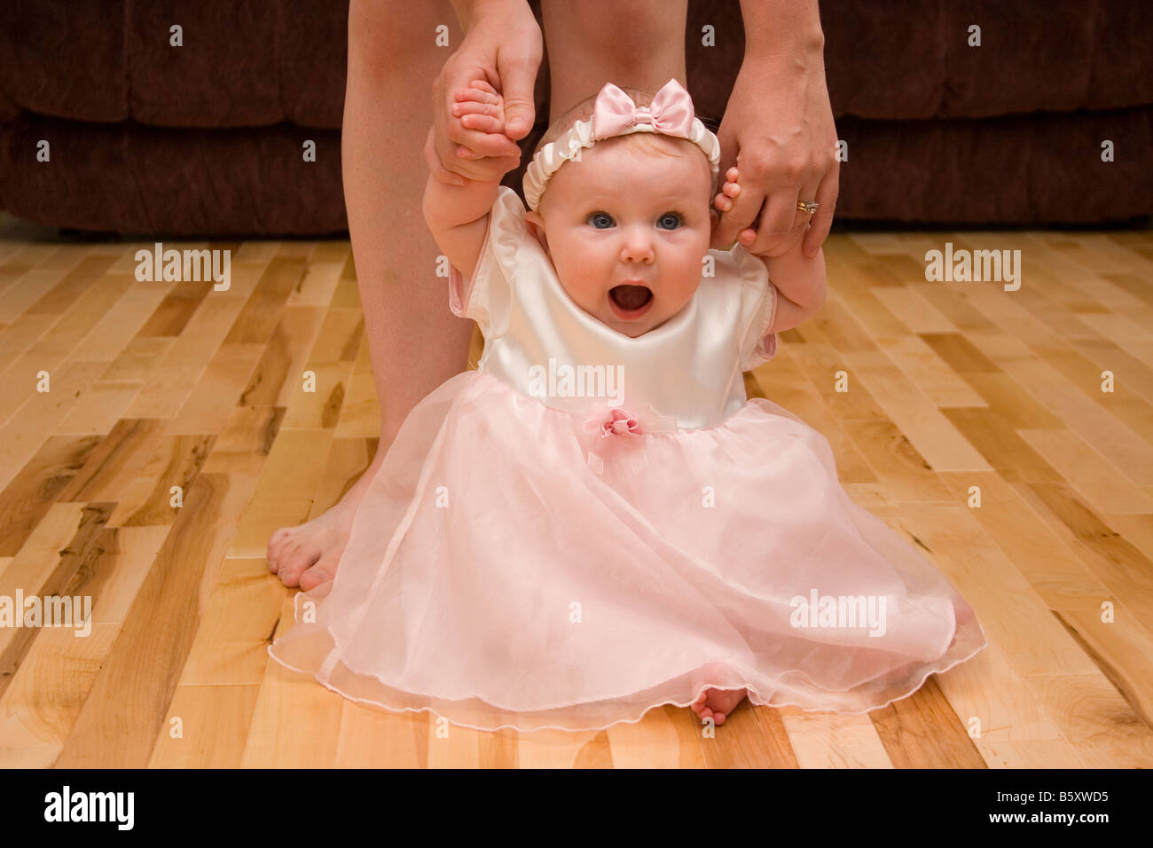 Baby sitting on floor looking surprised with mother holding her hands while learning to walk - Stock Image