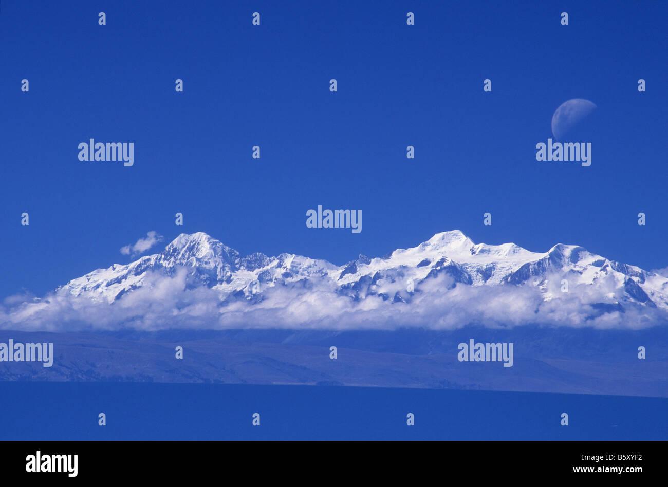 Moon rising over Mts Illampu (L), Ancohuma and Lake Titicaca, seen from Sun Island. Bolivia - Stock Image
