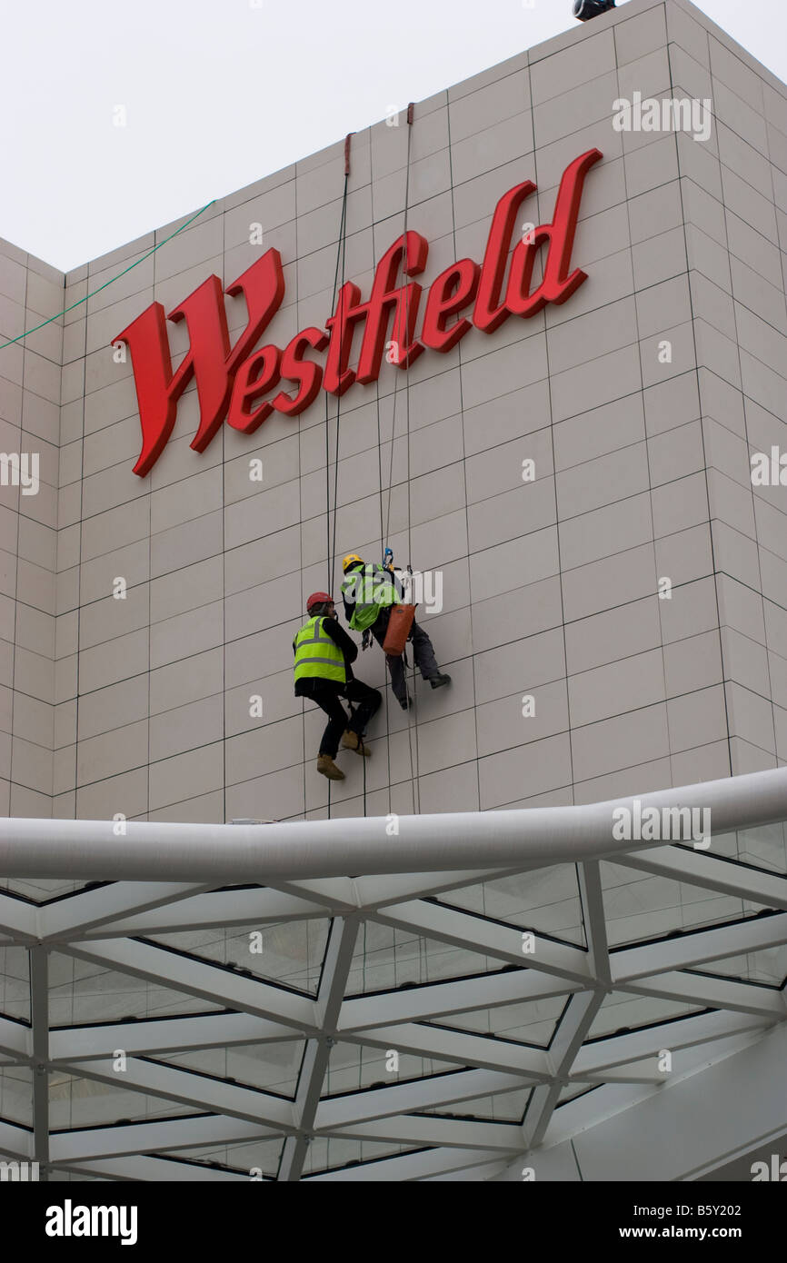 Westfield shopping centre in Shepherds Bush West London abseilers roped access technicians working on iconic Westfield Stock Photo