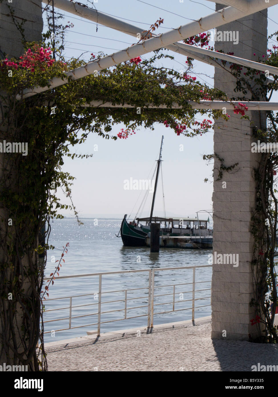 Traditional river boat at Passeio das Tagides seen through a whitewashed pergola with pink flowers, Oriente, Lisbon, - Stock Image