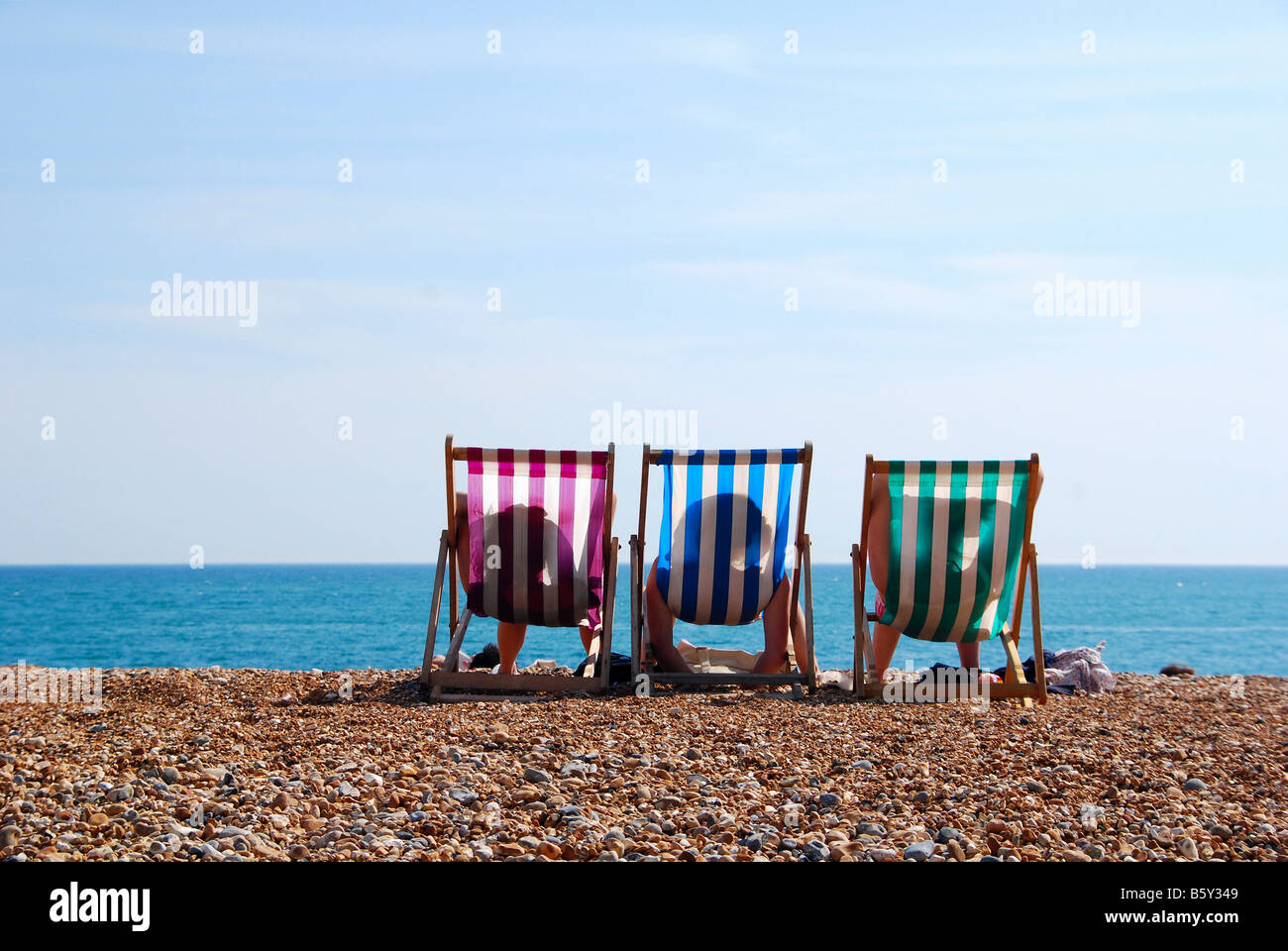 Three relaxing holiday deck chairs on beach. - Stock Image